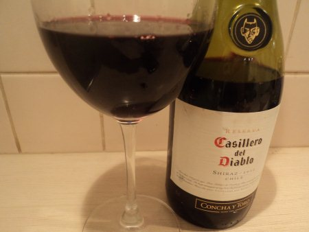 Бокал и бутылка красного сухого вина casillero del diablo